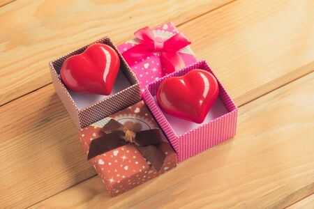 contain: Gift of love. hearty gift. A gift box with a red heart inside. On the wooden floor Stock Photo
