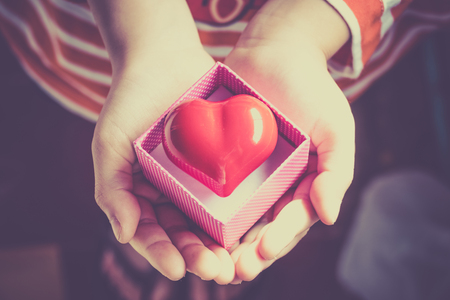 Red Heart in a gift box, in the hands of a girl. valentine background Stock Photo - 50659631