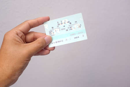 Hokkaido, Japan - September 3, 2018 : A hand holding a typical printed reserve seat train ticket issued at Hokkaido