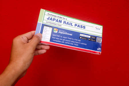 Penang, Malaysia - May 25, 2020 : Close up view of a hand holding a used Japan Rail Pass Exchange Order on red background at Gelugor