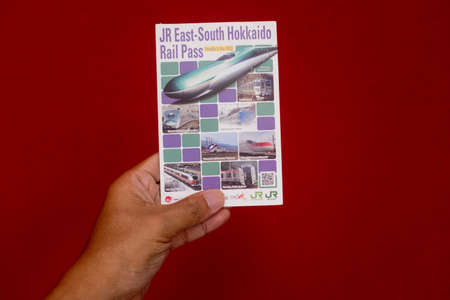 Penang, Malaysia - May 25, 2020 : Close up view of a hand holding a used JR East South Hokkaido Rail Pass on white background at Gelugor