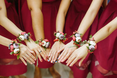 View of bridesmaid with little flower bouquets tied on their wrists Standard-Bild
