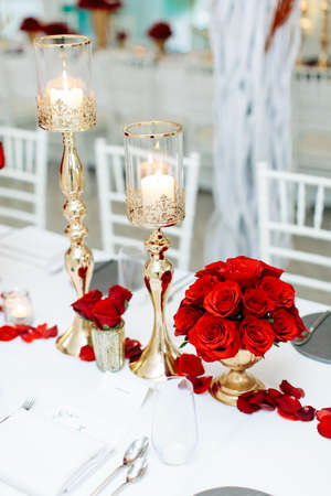 View of a beautiful table arrangement of red roses, white candles and table cloth during a wedding