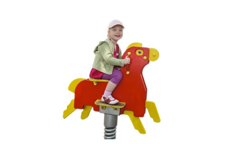 smiling happy child girl on a wooden horse isolated over white, copyspace Stock Photo - 9867071
