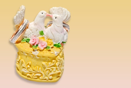 wedding invitation or card form with two kissing pigeons on the rings box over yellow-pink gradient background photo