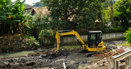excavator scrapping mud from river photo taken in Semarang Indonesia Stock Photo