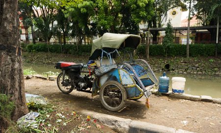 motorizado: motorized tricycles parks beside a dirty river photo taken in Semarang Indonesia Foto de archivo