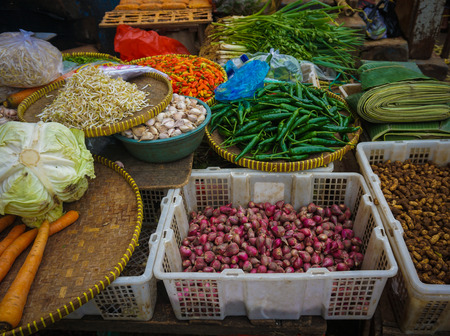 Green grocer sells various kind of vegetables,herbs and spices at traditional market in Jakarta Indonesia