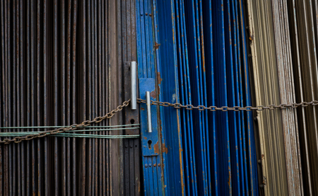 Blue and grey metal rolling door locked by chain photo taken in Jakarta indonesia Stock Photo