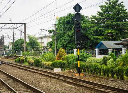 Kolej z kablem elektrycznym do podmiejskich linii otaczających drzewa i krzewy na stacji Depok Station zrobione w Indonezji Depok