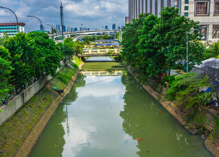 a river in the middle Jakarta near Central Park Mall with reflection of buildings and trees photo taken in Jakarta Indonesia