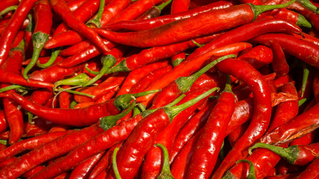 lots of fresh large red spicy chillis shot from overhead at outdoors market in traditional market in indonesia central java