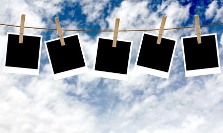 Blank photographs hanging on a clothesline against a blue sky