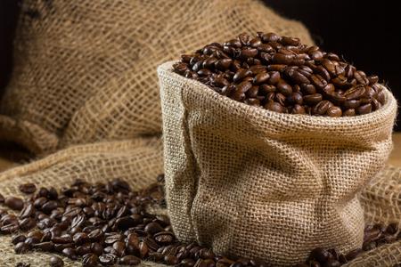 cafe colombiano: Negro granos de caf? tostado en un peque?o saco de arpillera