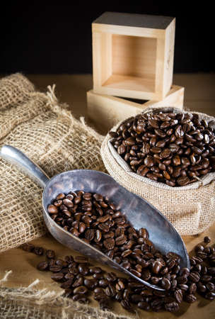 Black roasted coffee beans in a small burlap sack photo