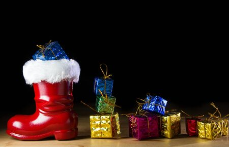 Red Santa boot and gifts on black background photo