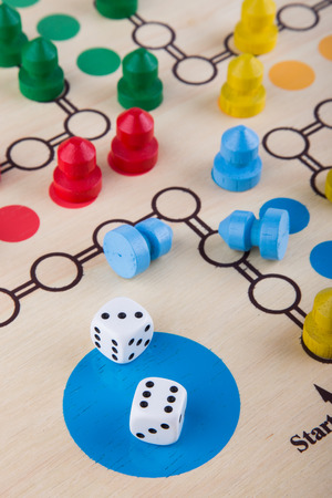 Colored board game figures with dice photo