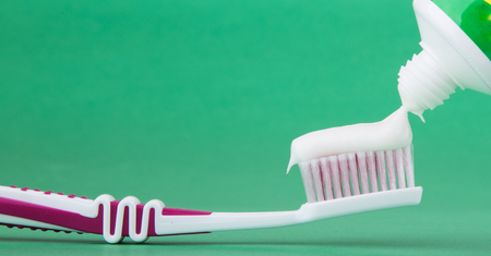 toothbrush with toothpaste isolated on a green background photo
