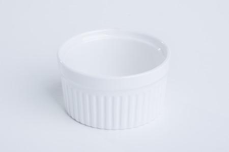 precarious: White ceramic bowl on white background Stock Photo