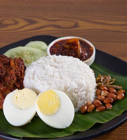 lemak: nasi lemak, a traditional malay curry paste rice dish served on a banana leaf