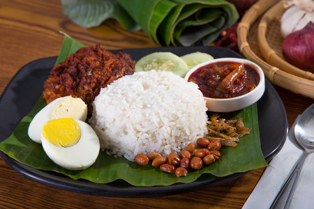 malay food: nasi lemak, a traditional malay curry paste rice dish served on a banana leaf