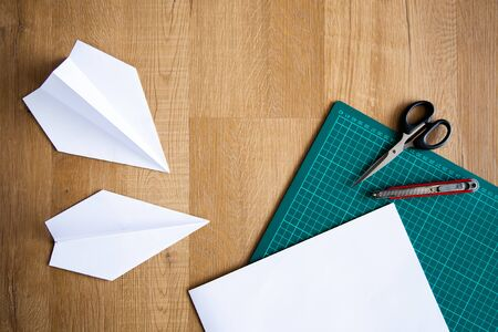 flatlay of paper plane on wooden background
