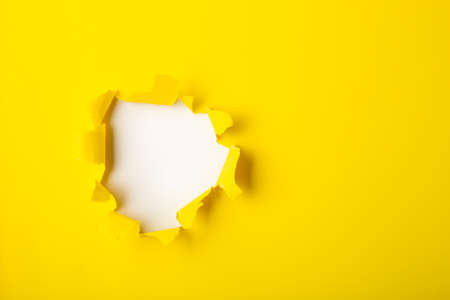 Torn hole and ripped of yellow paper with space for text with white background.