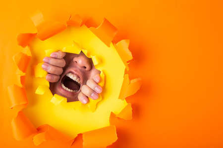 man screaming out from behind hole of orange paper Foto de archivo