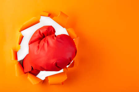 Punching boxing glove though over orange paper background