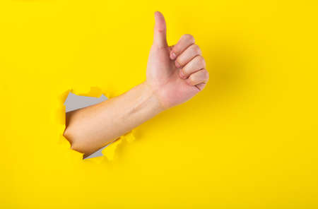 Hand showing a thumb up sign through a ripped hole in yellow paper background.
