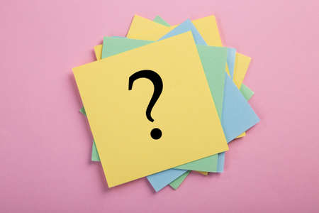 Question mark drawn on notepad. Over pink background with copy space. Imagens