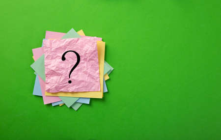 Question mark drawn on notepad. Over green background with copy space. Imagens