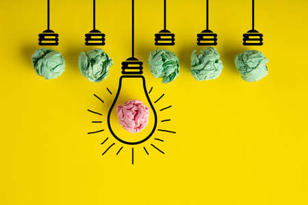 Inspiration concept crumpled paper light bulb metaphor for good idea on yellow background