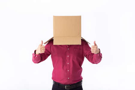 man in a red shirt with a cardboard box on his head makes a gesture with his hands isolated on white background