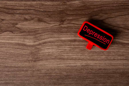 Red tag with Depression words on wooden bacground. Health Conceptual Archivio Fotografico
