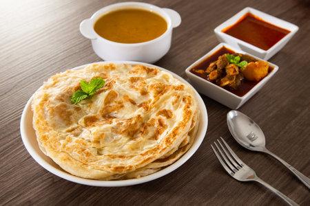 Roti Parata or Roti canai with lamb curry sauce - popular Malaysian breakfast Standard-Bild
