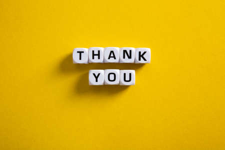 Block with word Thank You on yellow background