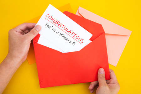 Hand open a red envelope with letter Congratulations You're a winner!