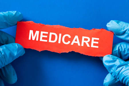 Doctor holds a red paper with the word MEDICARE, Medical Inusrance concept