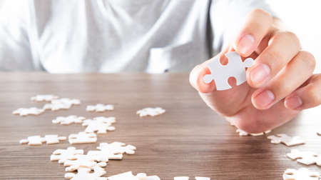 Closeup hand of man holding parts jigsaw puzzle. Business solutions, success and strategy concept