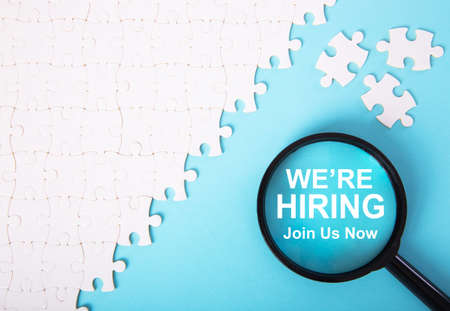 White jigsaw puzzle with word we're hiring. Recruitment Concept 免版税图像