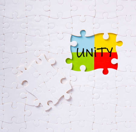 Puzzle pieces connected to each other with the word unity. Unity, synergy, integration or solidarity concept. 免版税图像
