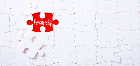 Jigsaw puzzle on red background with partnership word. Business Concept.