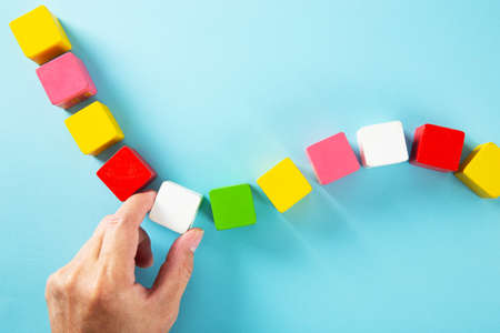 Hand arranging colorful wooden block. Business and Personal Development Concept. 免版税图像