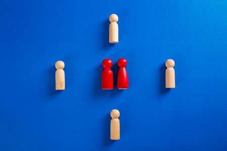 A wooden figure standing with a team to influence and empowerment. Concept of leadership