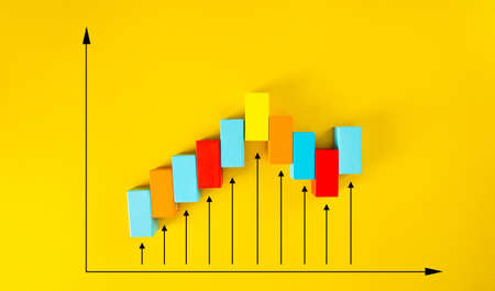 Wooden blocks arranged in an increasing graph on yellow background. Business growth, career growth or growth concept. 免版税图像