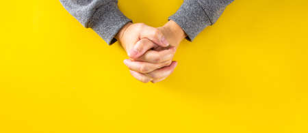 The hands of the man who was clinging to the prayer on the yellow background.Top view 免版税图像