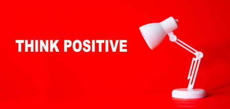 Desk lamp with word THINK POSITIVE on red background. Idea Conceptual 免版税图像
