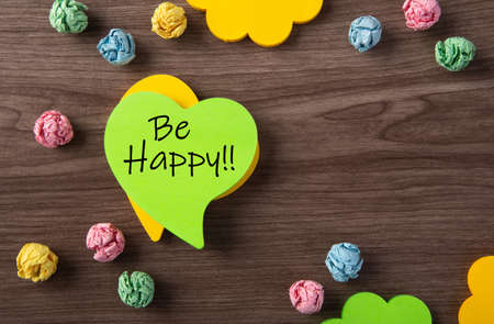 Green sticky note with word Be Happy on wooden table