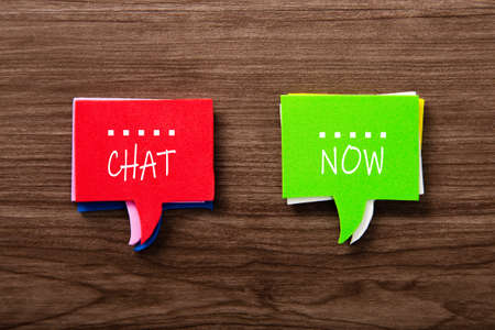 Bubble speech with word CHAT NOW on wooden background